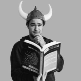 Man in viking hat holding a book upside down