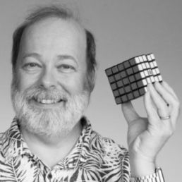 Man possing with a completed rubix cube